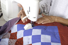 A quilter lifting a walking foot off of the quilt. Stock Image